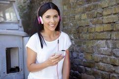 Młoda szczęśliwa uśmiechnięta kobieta z hełmofonami Obraz Stock