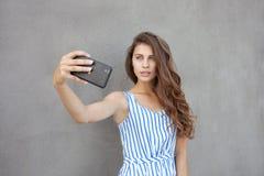 Młoda szczęśliwa uśmiechnięta piękna kobieta w światło sukni z długiej brunetki kędzierzawym włosy pozuje przeciw ścianie na ciep Fotografia Stock