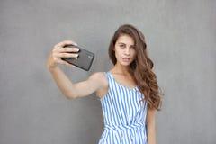 Młoda szczęśliwa uśmiechnięta piękna kobieta w światło sukni z długiej brunetki kędzierzawym włosy pozuje przeciw ścianie na ciep Obrazy Stock