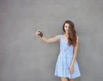 Młoda szczęśliwa uśmiechnięta piękna kobieta w światło sukni z długiej brunetki kędzierzawym włosy pozuje przeciw ścianie na ciep Fotografia Royalty Free