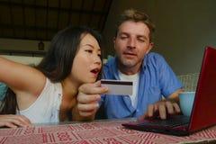 Młoda szczęśliwa, z podnieceniem mieszana pochodzenie etniczne para z Azjatyckimi Chińskimi internet bankowość i i zdjęcie stock
