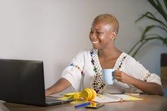 Młoda szczęśliwego, atrakcyjnego modnisia czerni afro Amerykańska kobieta pije w domu biurowy pracujący rozochoconego z laptopem  Zdjęcie Royalty Free