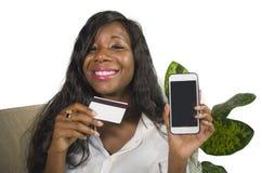 Młoda szczęśliwego i pięknego czarnego afrykanina kobiety Amerykańska leżanka w domu używać kartę kredytową dla kupować online i  fotografia royalty free