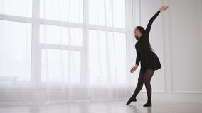 Młoda tancerz kobieta jest rozgrzewkowy up mięśnie plecy i ręki w sala zbiory