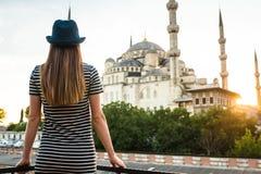 Młoda turystyczna dziewczyna z postaci pięknymi spojrzeniami od hotelu tarasu światowy sławny błękitny meczetowy Sultanahmet wewn fotografia stock