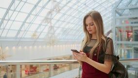 Młoda turystyczna kobieta w kapeluszu, z plecaków stojakami przy lotniskiem i uses smartphone Modniś dziewczyna sprawdza emaila,  zbiory