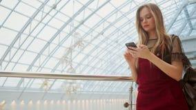 Młoda turystyczna kobieta w kapeluszu, z plecaków stojakami przy lotniskiem i uses smartphone Modniś dziewczyna sprawdza emaila,  zdjęcie wideo