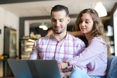 Młoda uśmiechnięta żona i mąż używa laptop przy kawiarnią i surfować fotografia royalty free