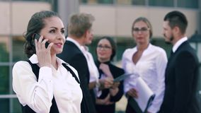 Młoda uśmiechnięta biznesowa kobieta dyskutuje jej pomyślnego pracującego dzień na telefonie i jej kolegach gawędzi w zbiory