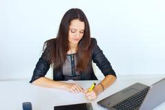 Młoda uśmiechnięta biznesowa kobieta przy biurowym biurkiem obrazy stock