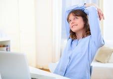 Młoda uśmiechnięta biznesowa kobieta relaksuje przy pracą Zdjęcia Stock