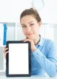 Młoda uśmiechnięta bizneswomanu mienia pastylka w rękach siedzi przy biurem Zdjęcia Royalty Free