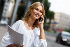 Młoda uśmiechnięta blond kobieta z telefonem komórkowym i papierami obrazy stock
