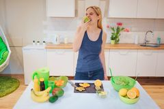 Młoda uśmiechnięta blondynki kobieta gryźć organicznie jabłka podczas gdy gotujący świeże owoc w kuchni zdrowe jeść jarosz zdjęcia royalty free