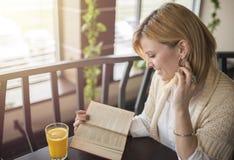Młoda uśmiechnięta blondynki kobieta w restauracyjnym czytaniu dr i książka obraz stock