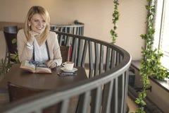 Młoda uśmiechnięta blondynki kobieta w restauracyjnym czytaniu pić kawa i książka obrazy royalty free