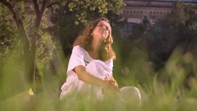 Młoda uśmiechnięta caucasian brunetka w parkowym obsiadaniu na trawie, greaming, myśleć