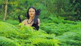 Młoda uśmiechnięta czarownica w czerni ubraniach w gąszczu paprocie wykonuje magicznych ruchy z jego rękami halloween zbiory
