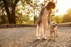 Młoda uśmiechnięta dama siedzi psa w parku i ściska w przypadkowych ubraniach obraz stock
