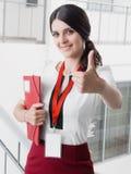 Młoda Uśmiechnięta dziewczyna Robić Pomyślni prac przedstawienia Gestykuluje Dużego kciuk Up Piękna Uśmiechnięta bizneswoman pozy zdjęcie stock