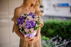 Młoda uśmiechnięta dziewczyna trzyma kosz fiołkowi kwiaty Zdjęcie Stock