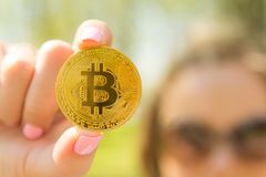 Młoda uśmiechnięta dziewczyna trzyma nowego menniczego bitcoin w jej ręce Zdjęcie Royalty Free