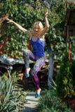 Młoda uśmiechnięta dziewczyna w barwionych leggings i błękita wierzchołku na piętach skacze w parku Zdjęcie Royalty Free