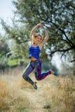 Młoda uśmiechnięta dziewczyna w barwionych leggings i błękita wierzchołku na piętach skacze w polu Zdjęcia Stock