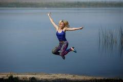 Młoda uśmiechnięta dziewczyna w barwionych leggings i błękita wierzchołku na piętach skacze na rzecznym brzeg obraz royalty free