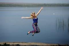 Młoda uśmiechnięta dziewczyna w barwionych leggings i błękita wierzchołku na piętach skacze na rzecznym brzeg zdjęcia royalty free