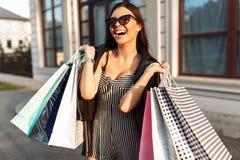 Młoda uśmiechnięta dziewczyna w okularach przeciwsłonecznych, cieszy się pomyślnego zakupy, fotografia stock