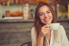 Młoda uśmiechnięta dziewczyna z filiżanką kawy Obrazy Royalty Free