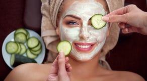 Młoda uśmiechnięta dziewczyna z kosmetyk maską przy zdroju salonem Obrazy Royalty Free