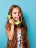 Młoda uśmiechnięta dziewczyna z zielonym handset zdjęcia stock
