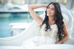Młoda uśmiechnięta kędzierzawa brunetki dama pozuje siedzieć Zdjęcia Stock