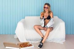 Młoda uśmiechnięta kobieta je kawałek pije soku obsiadanie na kanapie jest ubranym okulary przeciwsłonecznych pizza zdjęcia royalty free