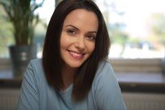 Młoda uśmiechnięta kobieta patrzeje prosto naprzód Zdjęcie Stock