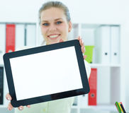 Młoda uśmiechnięta kobieta pokazuje pustego pastylka ekran komputerowego w biurze Fotografia Royalty Free