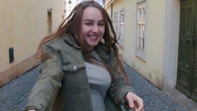 Młoda uśmiechnięta kobieta prowadzi jej chłopaka rzut ręcznie ulica i wysyła on ciosu buziak zbiory