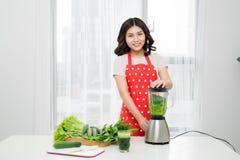 Młoda uśmiechnięta kobieta robi smoothie z świeżymi zieleniami w ble Zdjęcia Royalty Free