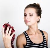 Młoda uśmiechnięta kobieta trzyma świeżą czerwoną wiązkę winogrona Zdjęcia Stock