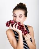 Młoda uśmiechnięta kobieta trzyma świeżą czerwoną wiązkę winogrona Zdjęcie Stock