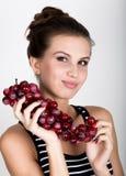 Młoda uśmiechnięta kobieta trzyma świeżą czerwoną wiązkę winogrona Zdjęcie Royalty Free