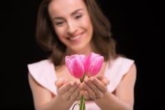 Młoda uśmiechnięta kobieta trzyma pięknych różowych tulipany na czerni Zdjęcie Stock