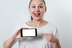 Młoda uśmiechnięta kobieta trzyma smartphone horizontally z białym ekranem z miejscem dla copyspace i punktami przy on palec zdjęcie royalty free