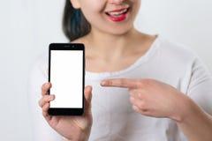 Młoda uśmiechnięta kobieta trzyma smartphone pionowo z białym ekranem z miejscem dla copyspace i punktami przy on palec fotografia royalty free