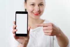 Młoda uśmiechnięta kobieta trzyma smartphone pionowo z białym ekranem z miejscem dla copyspace i punktami przy on palec obrazy royalty free