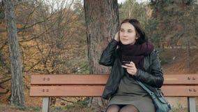 Młoda uśmiechnięta kobieta używa smartphone obsiadanie na ławce w parku Piękna europejska dziewczyna texting na telefonie zdjęcie wideo