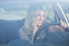 Młoda uśmiechnięta kobieta używa telefon w samochodzie Zdjęcia Royalty Free