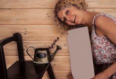 Młoda uśmiechnięta kobieta utrzymuje białego capboard, stoi blisko rocznika metalu podlewania puszki z kwiatonośną berberys pospo obraz stock